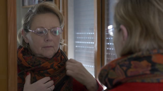 middle aged woman puts on a jacket in the mirror with serious expression - comparsa video stock e b–roll