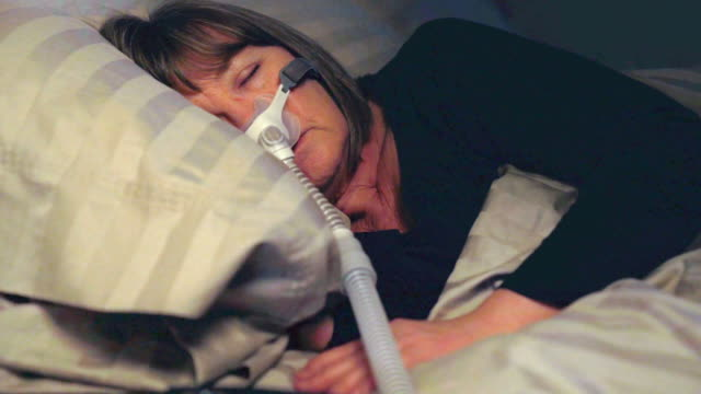 Middle Aged Woman Sleeping Soundly Using a CPAP Machine to Cure Her Sleep Apnea Middle Aged Woman Sleeping Soundly Using a CPAP Machine to Cure Her Sleep Apnea medical oxygen equipment stock videos & royalty-free footage