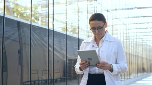Middle Aged Woman Walking with Computer Medium shot of serious middle-aged woman in lab coat and glasses working with tablet computer when walking through industrial greenhouse hallway, follow shot lab coat stock videos & royalty-free footage