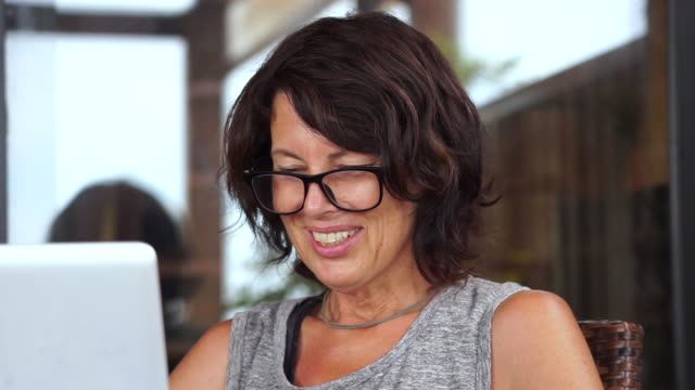 medelålders kvinna med glasögon slutar dator videosamtal från trädgården - rådig bildbanksvideor och videomaterial från bakom kulisserna