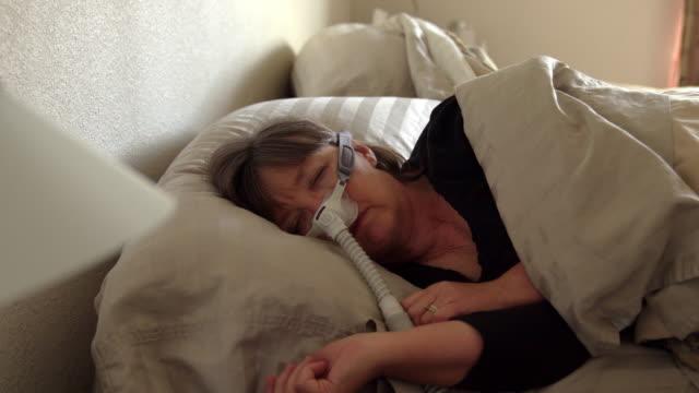 stockvideo's en b-roll-footage met middelbare leeftijd vrouw met slaapapneu in slaap in een bed het dragen van een cpap (continue positieve luchtweg druk) machine om te helpen in haar slaap - ventilator bed