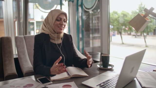 Middle Eastern business lady having video call in cafe - vídeo