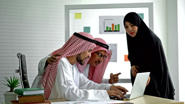 4K Middle Eastern Businessman And Businesswoman Having A Meeting And Using Laptop Computer Working In The Office