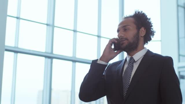 middle eastern businessman having phone conversation in office center - call center стоковые видео и кадры b-roll