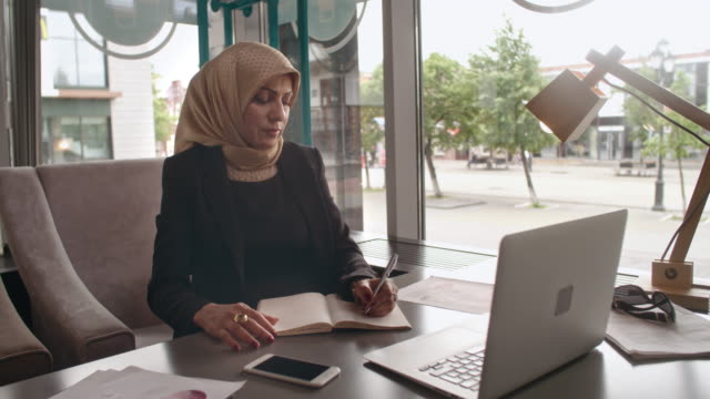Middle Eastern businesswoman doing research in cafe video