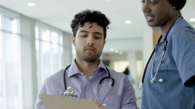 Middle Eastern Doctor Talking To Black Female Nurse video
