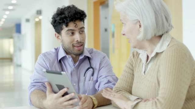 Middle Eastern Doctor Talking To Senior Female Patient A middle eastern male doctor is discussing a treatment plan with he female patient using a digital tablet. general practitioner stock videos & royalty-free footage
