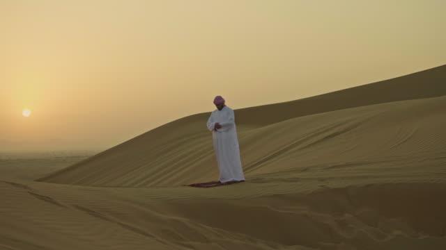 vídeos y material grabado en eventos de stock de hombre oriente orar al amanecer en el desierto - islam
