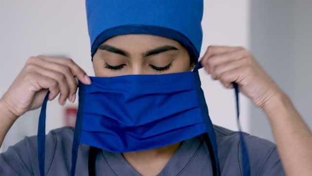 vídeos de stock e filmes b-roll de middle eastern medical professional tying her mask - enfermeira