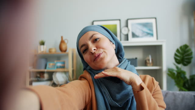 pov of middle eastern woman in hijab taking selfie at home looking at camera - selfie stock videos & royalty-free footage