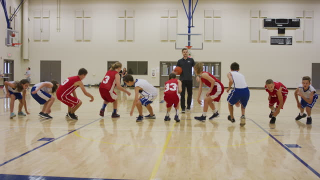 Middle school boys and girls running lines in a gymnasium Mixed group of middle school basketball players running lines during a drill practice drill stock videos & royalty-free footage