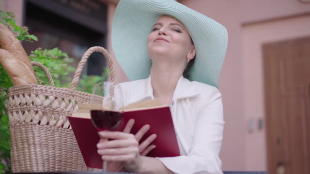 Middle shot of smiling woman drinking wine and reading book. Portrait of happy stylish Caucasian lady in turquoise hat enjoying vacations outdoors on sunny summer day. Middle shot of smiling woman drinking wine and reading book. Portrait of happy stylish Caucasian lady in turquoise hat enjoying vacations outdoors on sunny summer day. one mid adult woman only stock videos & royalty-free footage