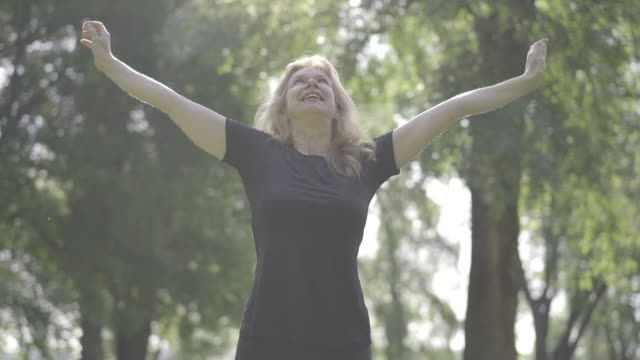 Middle shot portrait of happy mid-adult sportswoman doing exercises in sunlight outdoors. Smiling blond Caucasian woman training in sunny summer park. Lady raising hands up and down. Healthy lifestyle. Middle shot portrait of happy mid-adult sportswoman doing exercises in sunlight outdoors. Smiling blond Caucasian woman training in sunny summer park. Lady raising hands up and down. Healthy lifestyle. one mid adult woman only stock videos & royalty-free footage
