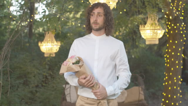 middle shot portrait of nervous caucasian man standing with bouquet of roses and checking time. loving romantic curly-haired boyfriend waiting for girlfriend in summer evening. cinema 4k prores hq - нетерпеливый стоковые видео и кадры b-roll