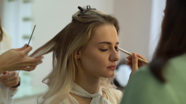 middle shot portrait of young woman getting professional service in beauty salon - аксессуар для волос стоковые видео и кадры b-roll