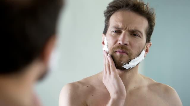 medelålders skäggig man applicera raklödder på ansikte, morgonritual, spegel - skägg bildbanksvideor och videomaterial från bakom kulisserna