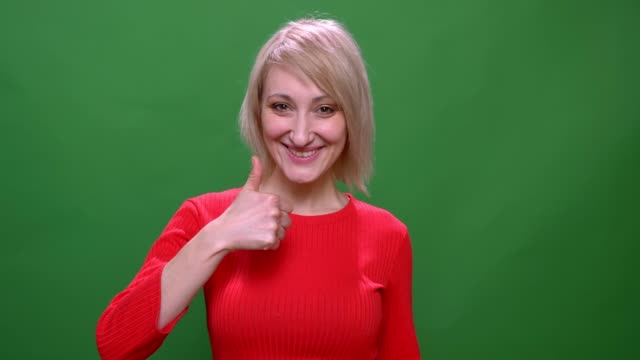 middle-aged blonde short-haired model gestures thumb-up sign isolated on green background. - occhiata laterale video stock e b–roll