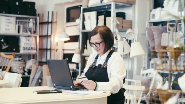 vídeos y material grabado en eventos de stock de empresario de mediana edad haciendo las finanzas en una tienda de decoración para el hogar - gerente de cuentas
