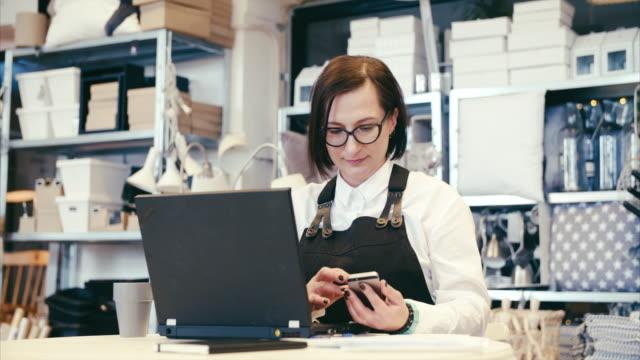 aziende di mezza età che utilizzano smartphone e computer (rallentatore) - owner laptop smartphone video stock e b–roll
