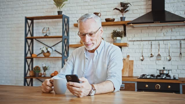 Middle-aged businessman drinking coffee, working online on smartphone or having rest browsing news, sitting at table of kitchen