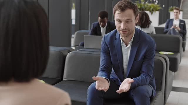 medelålders affärsman prata med oigenkännliga kvinnliga medarbetare - formella kontorskläder bildbanksvideor och videomaterial från bakom kulisserna