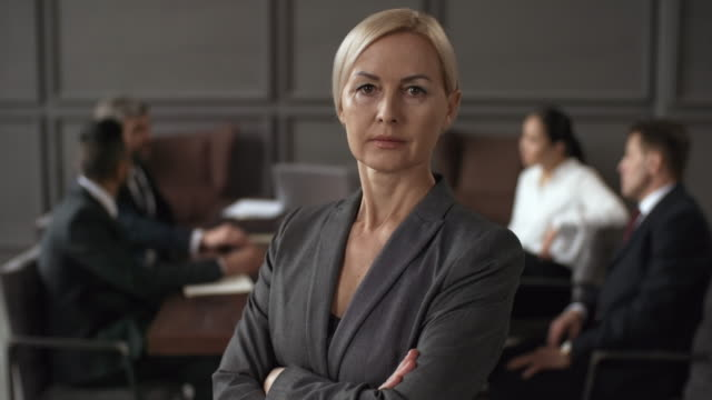 Middle-Aged Caucasian Female Executive Posing during Business Meeting Portrait shot of middle-aged blonde Caucasian career lady in business suit standing in meeting room with folded arms, looking at camera with confidence and colleagues sitting and talking in background authority stock videos & royalty-free footage