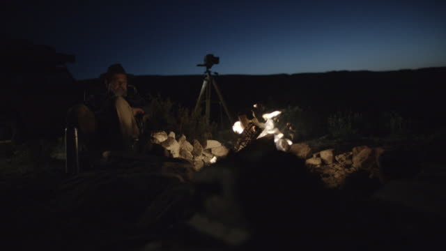 Middle-Aged Caucasian Male Sits by Campfire video