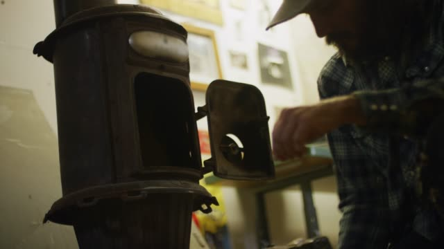 A Middle-Aged Caucasian Man Picks up Wood Kindling and Places It in a Wood Burning Stove in a Workshop