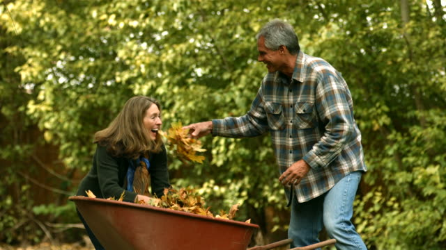 Middle-Aged couple throwing fall leaves, slow motion video