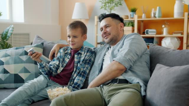 padre ragazzo di mezza età che guarda la tv con un figlio allegro che si rilassa sul divano in casa - padre single video stock e b–roll