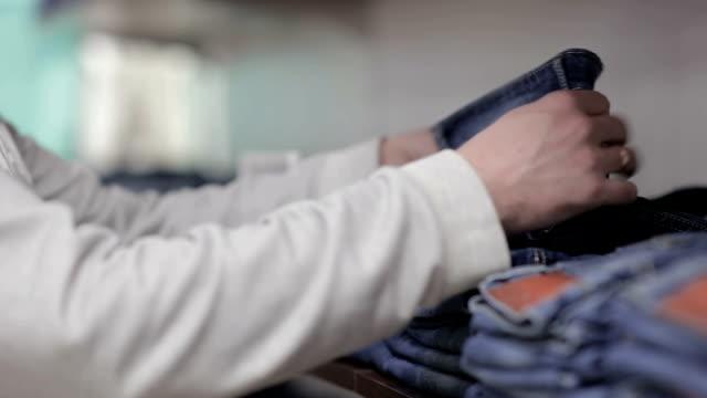 Medio-hombre anciano elige vaqueros en una tienda - vídeo