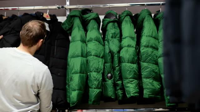 medio invecchiato uomo sceglie una calda giacca in negozio - abiti pesanti video stock e b–roll