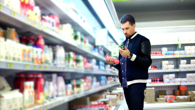 A middle-aged man chooses milk in a dairy department in plastic packaging video