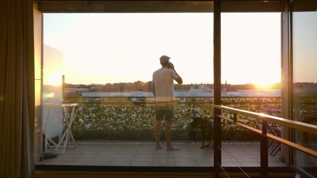 uomo di mezza età in pantaloni corti che parla al cellulare a casa mentre esce sulla terrazza al tramonto accompagnato dal suo cane - terrazza video stock e b–roll