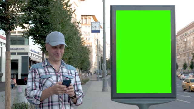vídeos de stock e filmes b-roll de middle-aged man stands on city street next to billboard and clicks on smartphone - led painel