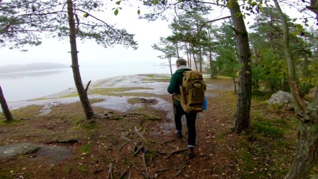 霧の秋の朝の海の岩の海岸に双眼鏡で野生動物を見て中年男。 - バードウォッチング点の映像素材/bロール