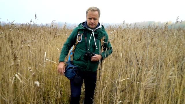 中年男、バックパックとを葦を通過します。 - バードウォッチング点の映像素材/bロール