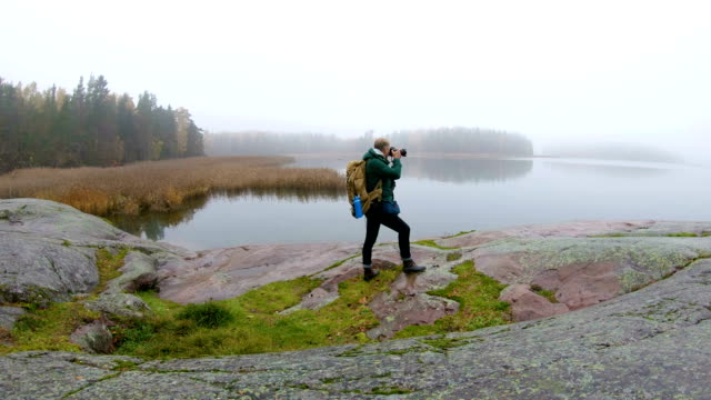A middle-aged man with a backpack photographing wildlife on a rocky shore