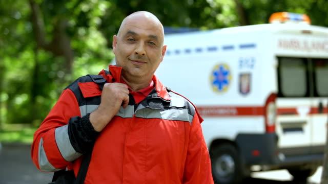 カメラ、緊急医療サービスのためにポーズ中年救急救命士 - 救急救命士点の映像素材/bロール