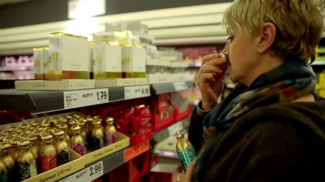 middle-aged woman chooses perfume for yourself video