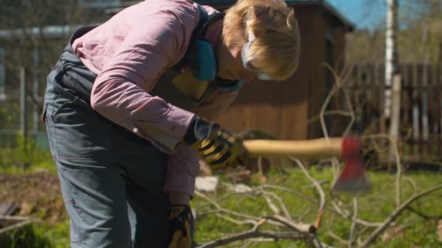 orta yaşlı kadın balta ağacı dalları doğrama - şömine odunu stok videoları ve detay görüntü çekimi