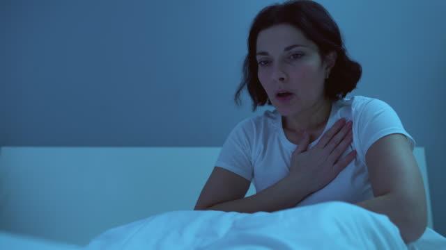 stockvideo's en b-roll-footage met vrouw van middelbare leeftijd die pijn op de borst in bed heeft, die hartgezondheidsproblemen lijdt - ongezond leven