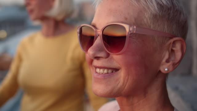 vídeos y material grabado en eventos de stock de mujer de mediana edad con gafas de sol - cabello corto