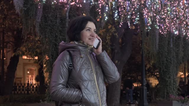 A middle-aged woman takes out a smartphone and talks. In evening time