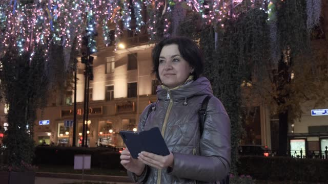 Middle-aged woman taking pictures of street decorations on smartphone