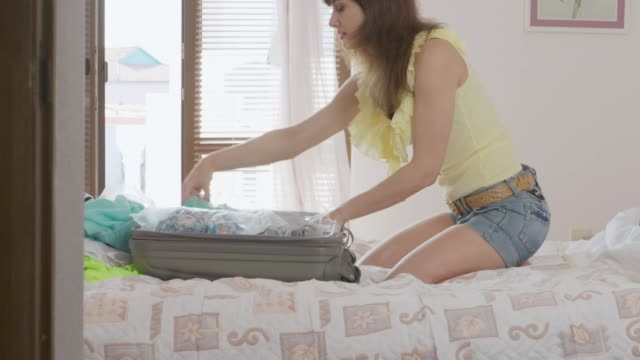 Middle-aged woman traveller unpacking a suitcase sitting on the bed video