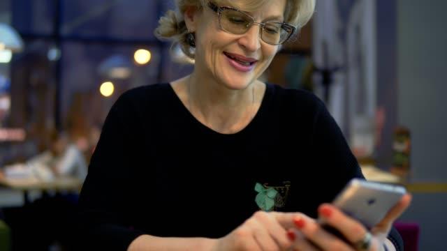 en medelålders kvinna använder mobiltelefoner på ett café. - 50 54 år bildbanksvideor och videomaterial från bakom kulisserna