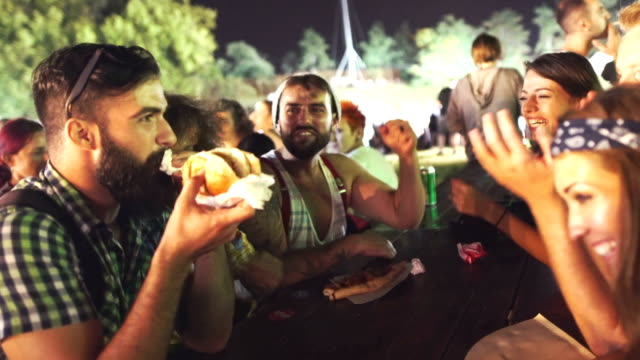 Midnight snack. Closeup of group of young adults having a snack on a night out. They are sitting outdoors at a festival, having fun while eating hot dogs and pizzas. hot dog stock videos & royalty-free footage