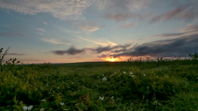 Midnight sun on the horizon and rising with colorful clouds video