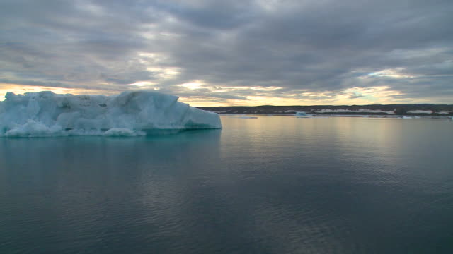 Midnight sun sailing with big icebergs in foreground Greenland video